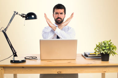 man in a office doing a no gesture sign